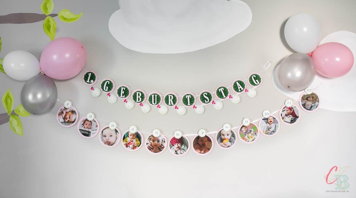 Zwei handgemachte Girlanden und Luftballons als Dekoration für die Party zum 1. Geburtstag.